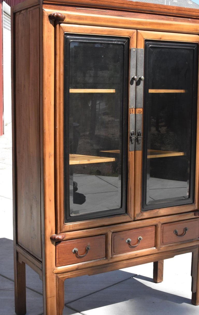 A Ming style solid wood cabinet with glass doors and removable shelves. Hua Li Rosewood on drawer fronts and top. Three full length drawers. Sophisticated black frames around glass doors. Carved thin lines on the top. Half lotus knobs hold the