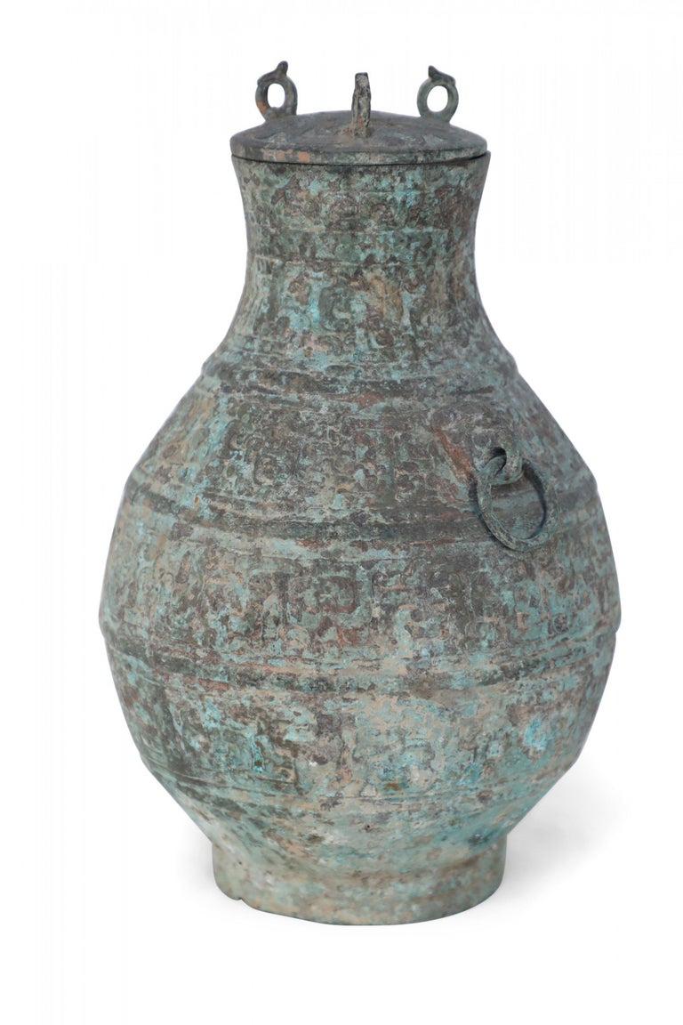 Antique Chinese Han Dynasty-style verdigis bronze ritual wine vessel with raised archaistic patterns, accented with two rings and topped with a lid bearing three bird-form finials.