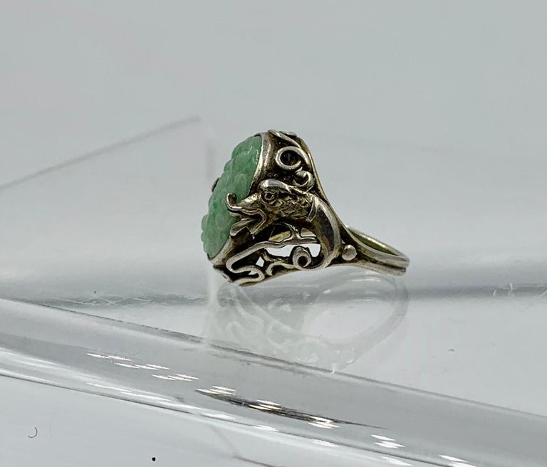 This is a wonderful and rare Ring with a central carved Jade in a flower motif.  The silver setting for the jade is extraordinary with a fantastic Dragon motif.  The dragons are on either side of the jade.  Their open mouth holds the jade.  The
