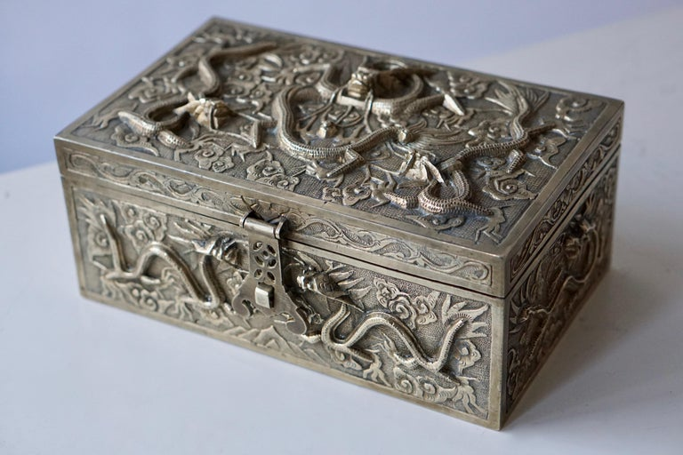 An exceptional, fine and impressive Chinese Export jewelry box. This exceptional Chinese Export silver plated metal box has a rectangular form. The surface of this box is embellished with dragons and flowers. The box is fitted with a hinged