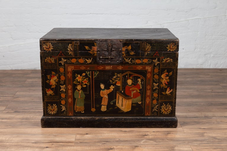 An antique Chinese large decorated black lacquered trunk from the early 20th century, with chinoiserie decor. Born in China during the early years of the 20th century, this trunk features an exquisite and colorful chinoiserie decor depicting court