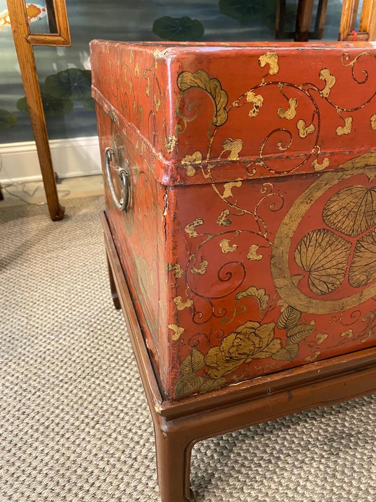 A beautiful and striking red leather trunk, circa 1930s, with hand painted gold crests from the Tokugawa family, with scrolling vines. While Tokugawa family crests are Japanese, I believe this trunk is Chinese. The crests are an iconic pattern,