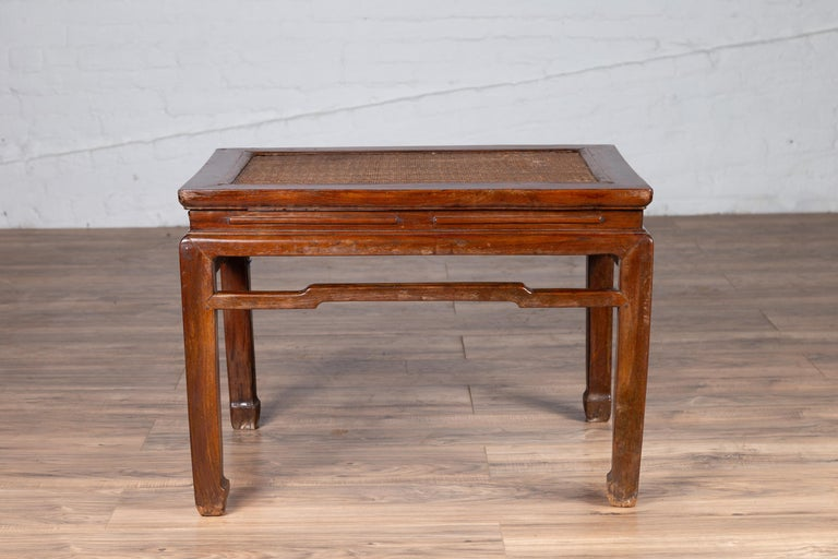 An antique Chinese Ming Dynasty style waisted side table from the early 20th century, with woven rattan top, humpbacked stretcher and horse hoof legs. Born in China during the early years of the 20th century, this elegant side table features a woven