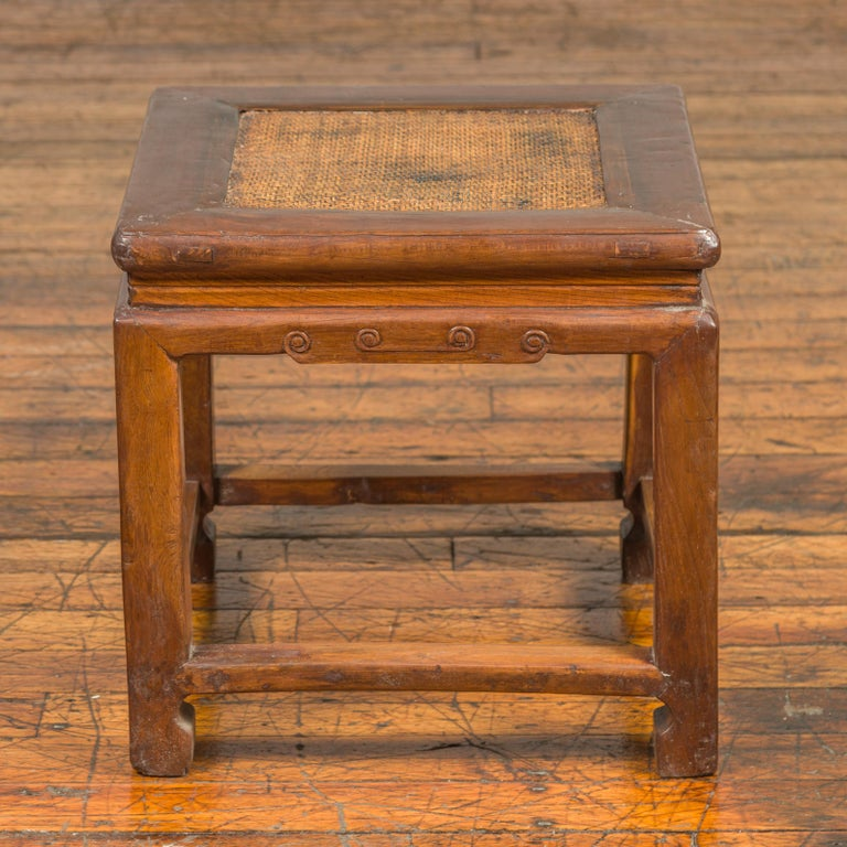 An antique Chinese Ming Dynasty style wooden waisted stool from the early 20th century, with rattan inset, horse hoof legs and cloud motifs. Born in China during the early years of the 20th century, this stool features a woven rattan square top