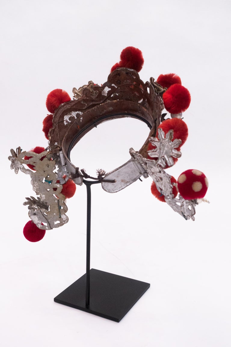 Chinese opera theatre headdress in turquoise papier mâché with red colored pom poms and faux pearls, early 20th century, mounted on a custom black painted metal base.