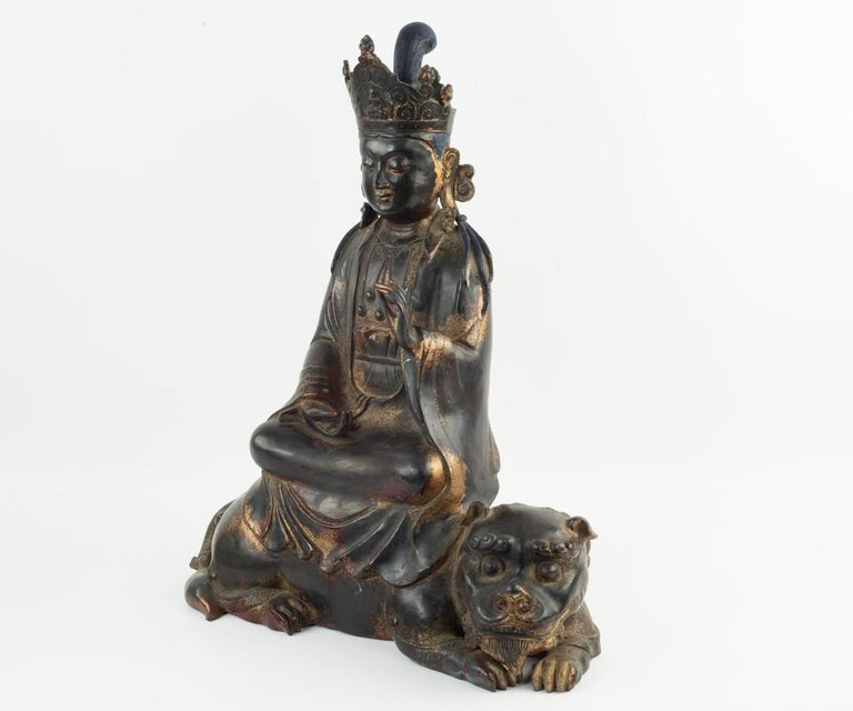 Offered is this large antique parcel gilt seated Quan Yin (Guanyin) wearing ornate garlands and a crown with Buddha. She has a beautiful face, downward gazing eyes, gesturing hands, seated upon a lotus flower and a recumbent lion. There is still