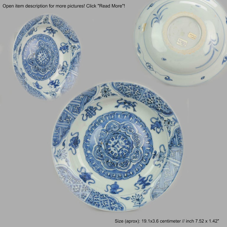 A blue and white late Ming plate with a nice and rare decoration. Lifted base. With a broad, unglazed firing ring. In its centre a raised, convex section. Decorated in underglaze blue, with geometric motifs, flowers and good fortune Buddhist symbols