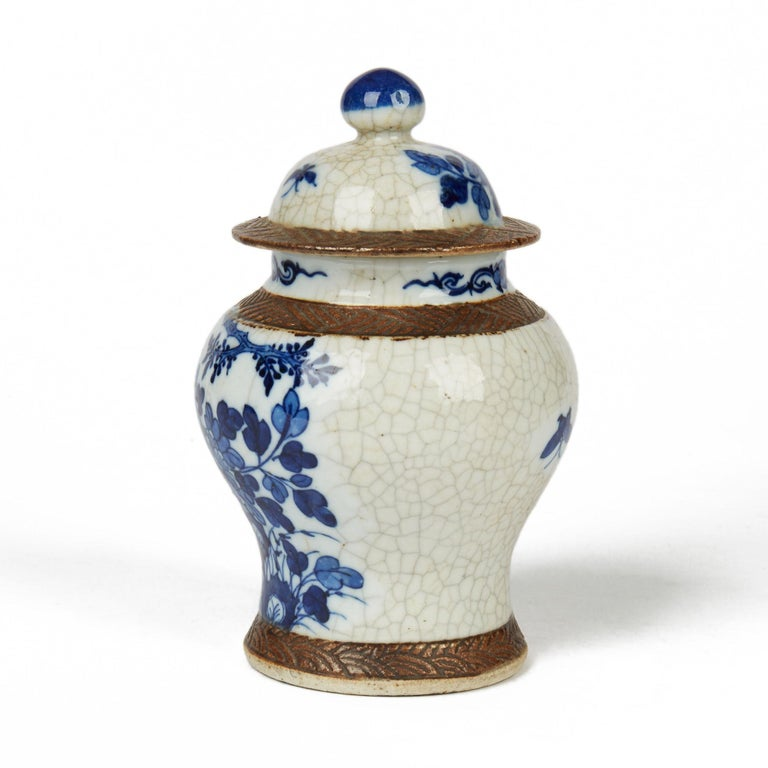 A very fine antique Chinese porcelain lidded ginger jar of rounded bulbous shape with hat shaped cover painted in blue and white with a tree and flowering shrubs on a cracquel ground and with matted brown patterned banding around the edges. The jar