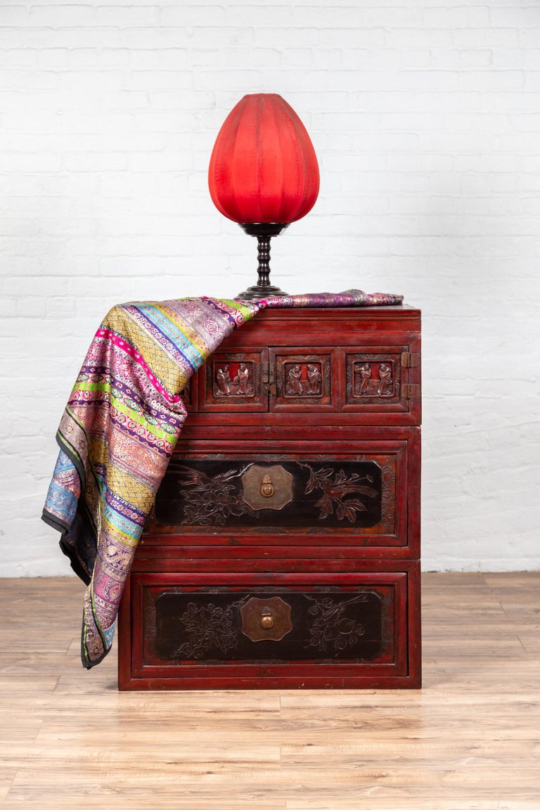 A Chinese antique red and black lacquered three-section chest with carved figures. Featuring a lovely red lacquered body, beautifully accented with black tones, this linear Chinese chest is made of three independent sections. The upper part is