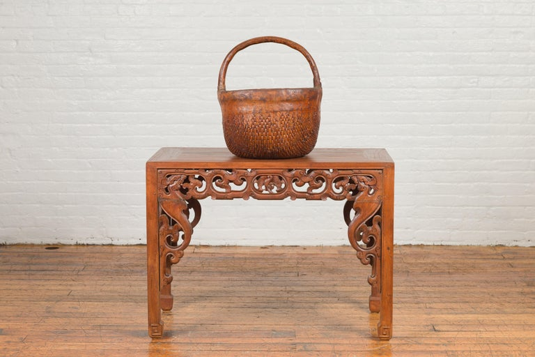 An antique Chinese carrying basket from the 19th century, with intricate woven rattan design. Created in China during the Qing Dynasty, this Chinese carrying basket charms us with its rustic appearance. A large handle is resting upon a rattan body