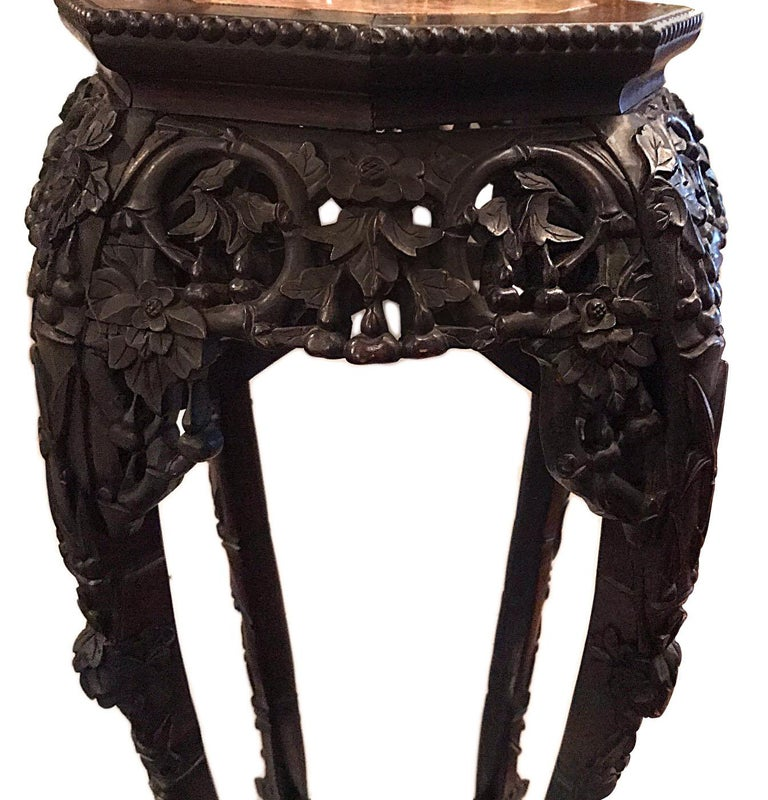 A 19th century Chinese carved wood stand with rose marble top.  Measurements: Height 37.5