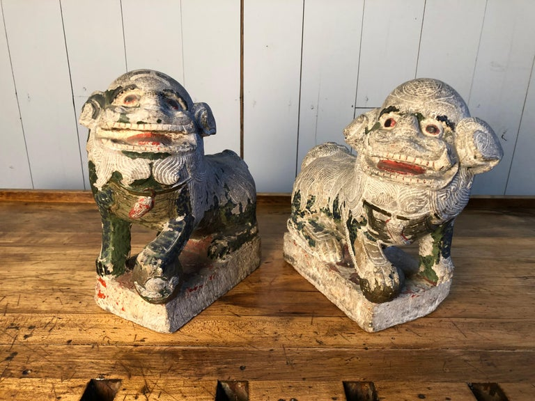A pair of carved stone Foo Dogs with traces of polychrome painted finish, 19th Century or earlier. Each seated figure with a front paw resting on a ball, facing opposite directions.