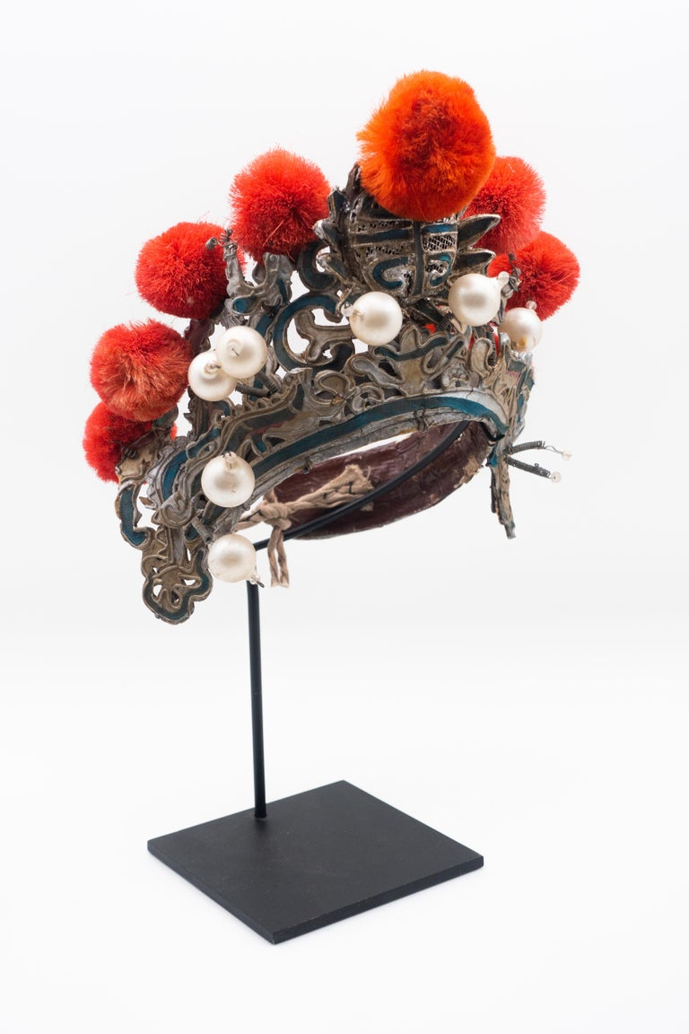 Chinese opera theatre headdress in turquoise with coral colored pom poms along with faux pearls, early 20th century, mounted on a custom black painted metal base.