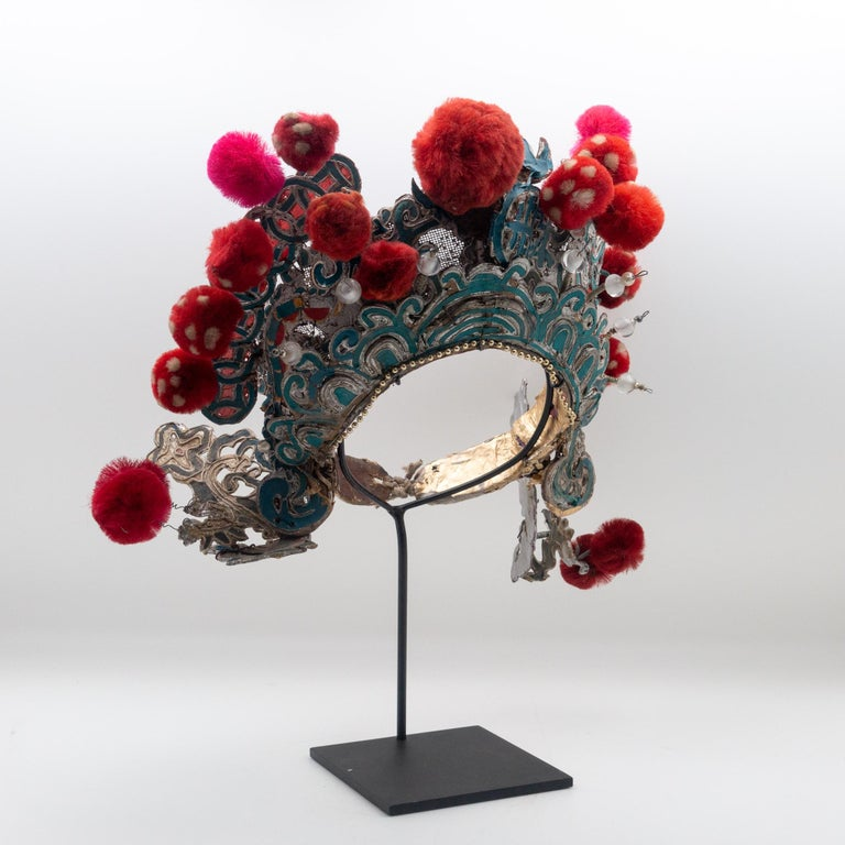 Chinese opera theatre headdress in turquoise and silver colors with red and fuchsia colored pom poms along with faux pearls, early 20th century, mounted on a custom black painted metal base.