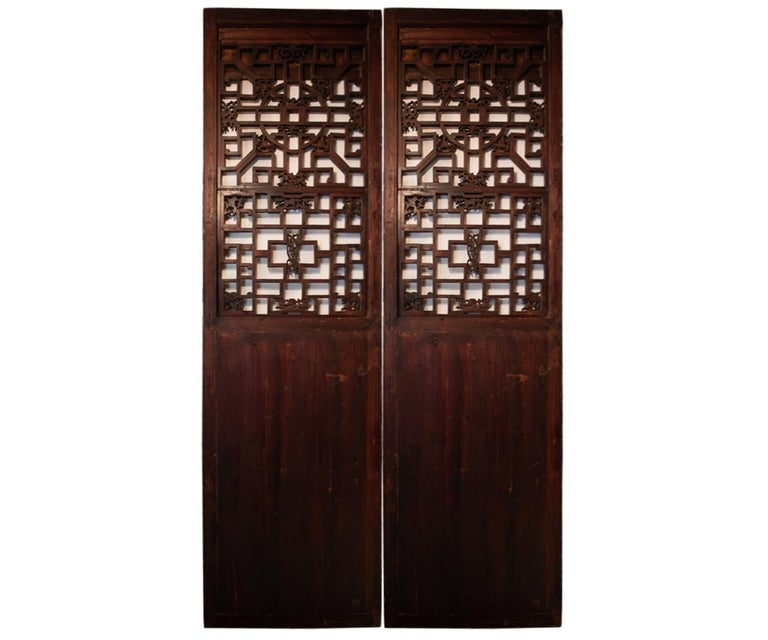 Antique hand carved pair of elm wood screen doors with two carved urns and a flower in the lower panel. The top section is formed by the Chinese longevity pattern on screen with more flowers on the screen. Often these types are seen either at a