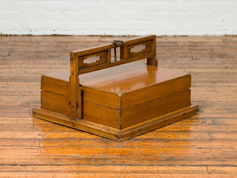 An antique Chinese wooden lunch box from the early 20th century, with large pierced handle and plinth. Born in China during the early years of the 20th century, this lidded wooden lunch box features a linear silhouette, perfect accented with