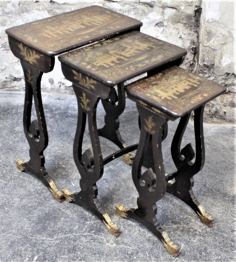 This antique set of lacquered nesting tables was made by Wong Kwoko Hing from Canton China in circa 1910 in the period chinoiserie style. These graduated nesting tables are constructed of a very light softwood which have hand painted gilt tops over