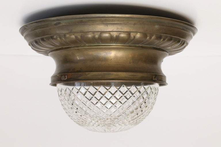 Repoussé flush mount light: brass fixture circled by repoussé decoration and finished with unusually deep cut-glass dome. This charming circa 1890 French light's quirky proportions and elegant details will set the tone of a room. Perfect for small