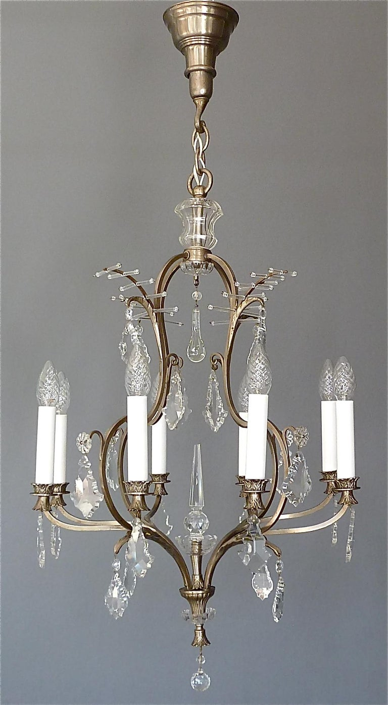 Beautiful classical and antique eight-light chandelier made of patinated metal and hand-cut faceted crystal glass, manufactured in Austria around 1910-1920. This chandelier with lovely details especially the palm-leaf crown motif on top and the
