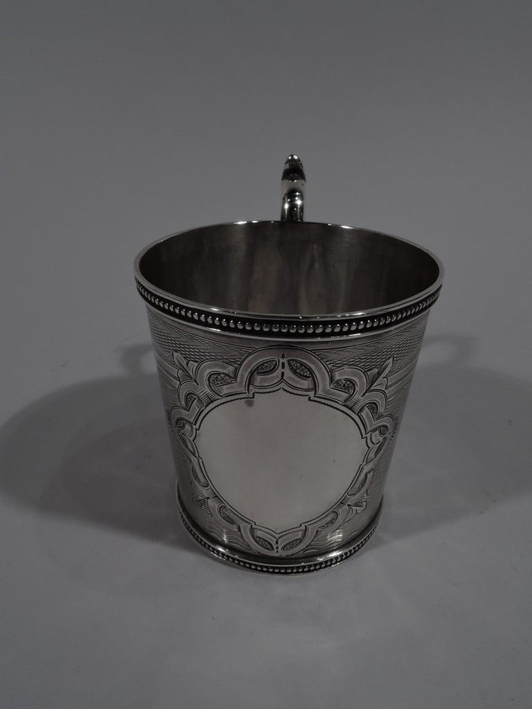 Classical coin silver baby cup. Made by John L. Westervelt in New York, circa 1860. Straight and gently tapering sides, capped s-scroll handle, and beaded rims. Two rondels interspersed with fleurs de lys and inset with male and female Renaissance