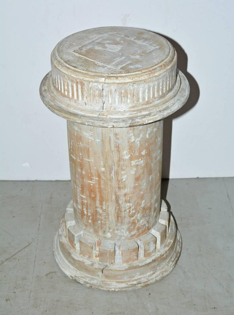 The antique column plinth, pedestal or base in the classical style is encircled at the bottom with dentils and at the top with a fluted design. White paint has been partially removed. Can be used for a small side table base, plant or sculpture