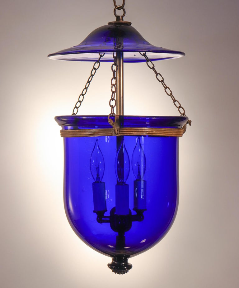 A striking cobalt blue hand blown glass bell jar lantern with its original smoke bell and rolled brass band, circa 1890. Originally for candlelight, this antique pendant has been newly electrified and casts a warm light from its three-bulb
