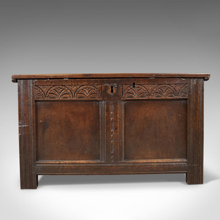 This is an antique coffer, an English oak, joined chest. A trunk dating to the late 17th century, circa 1700.  Mid-sized oak chest displaying rich, dark color Pegged joint construction with grain interest throughout Two panel chest with a