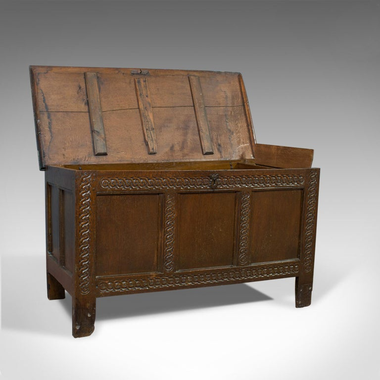 This is an antique coffer, a late 17th century, English oak, joined chest. A Charles II trunk dating to circa 1685.  Substantial oak chest displaying rich, dark colour Pegged joint construction with grain interest throughout Triple panel chest