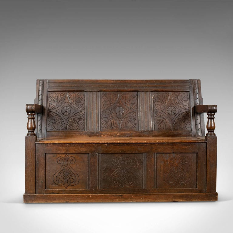 This is an antique coffer settle, an English oak bench chest seat dating to the early 18th century circa 1700 and later.  Good color in the lustrous wax polished finish Carved interest with a desirable aged patina Pegged and panelled