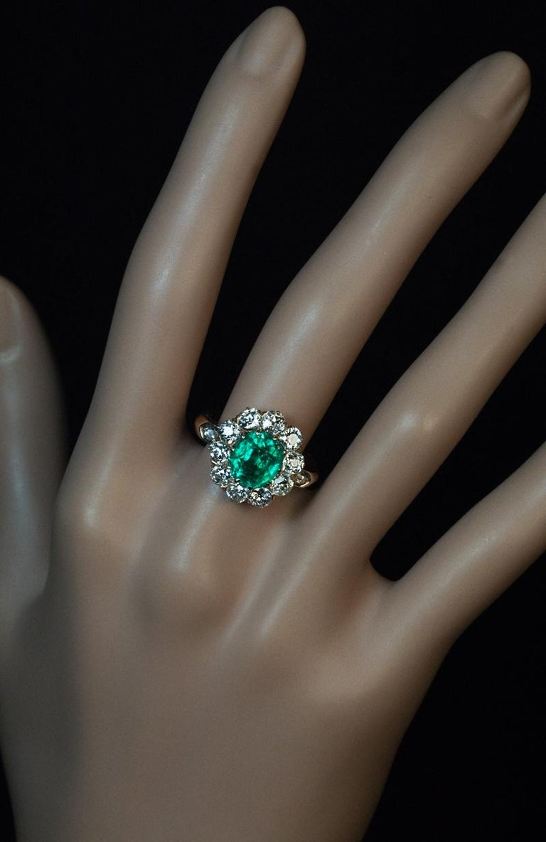 Made in Vienna, Austria in the 1890s. This classic gold cluster ring from the Victorian era features an oval Colombian emerald of excellent color, clarity and saturation. The emerald is surrounded by sparkling old European and old mine cut diamonds.