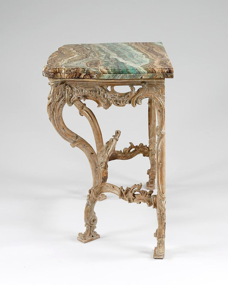A fine quality serpentine fronted giltwood console table designed in the French manner. Beautifully carved in the Rococo manner with entwined C-scrolls. The marble top is possibly later, European,