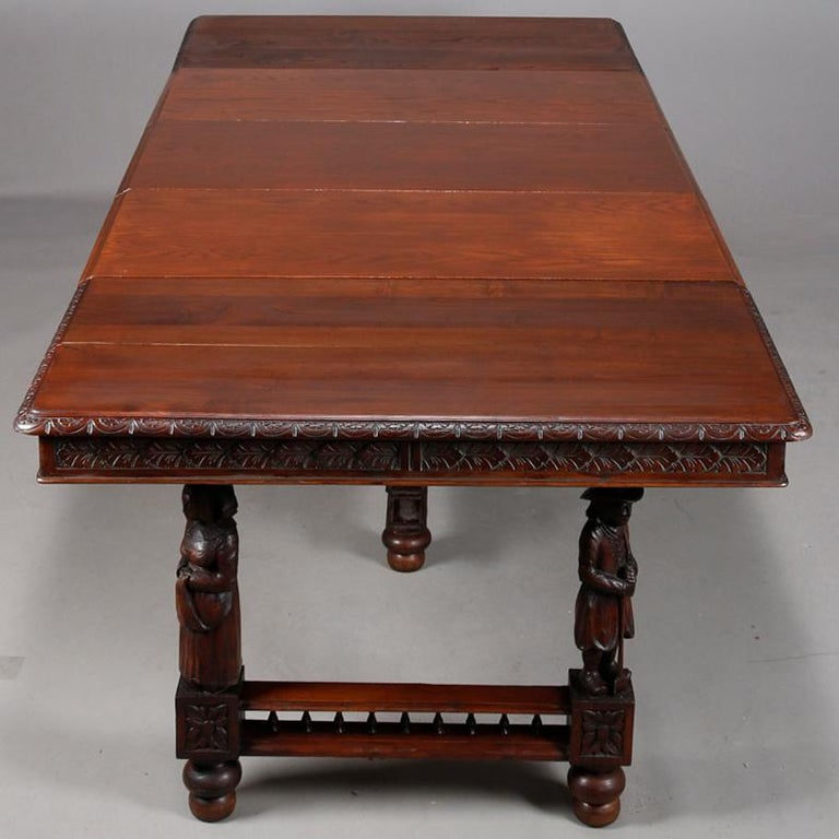 An antique Continental extension dining table offers oak construction with carved foliate skirt surmounting base having sculptured figural legs, accommodates three 18