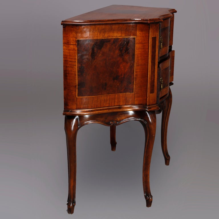 An antique Continental side stand offers walnut construction in serpentine form having shaped top over burl inlaid and crossbanded double drawer chest having foliate carved apron, raised on cabriole legs terminating in scroll feet, circa