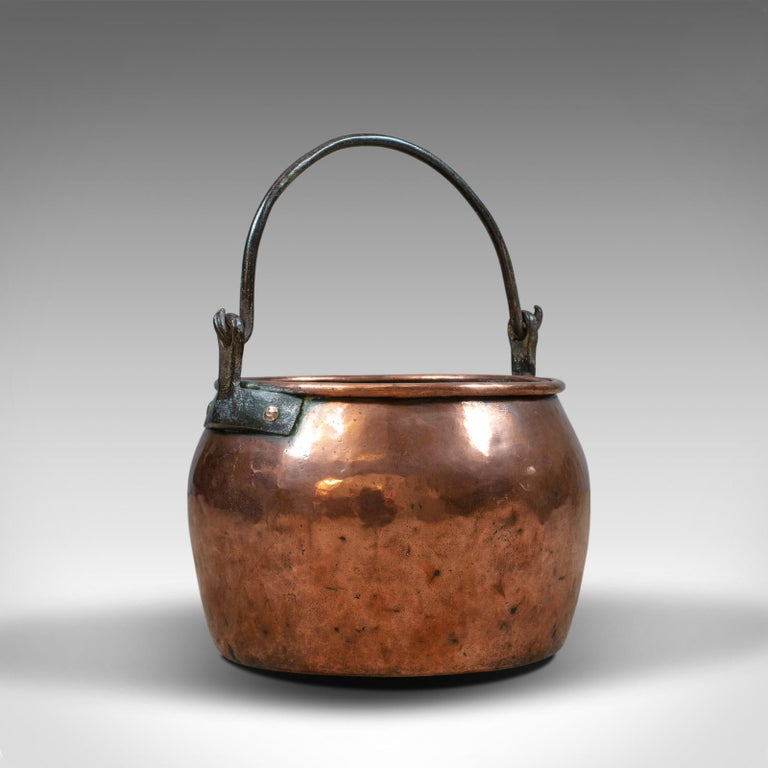 This is an antique copper cauldron. A heavy, English, Georgian pot with iron handle, ideal as a fireside log or coal scuttle, dating to the 18th century.