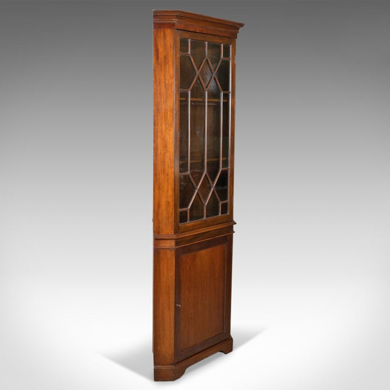 This is an antique corner cabinet, a glazed display cabinet, Edwardian in the Georgian Taste, English dating to circa 1910.  Mahogany with a deep rich lustre in the wax polished finish Plain canted corners display grain interest beneath a modest