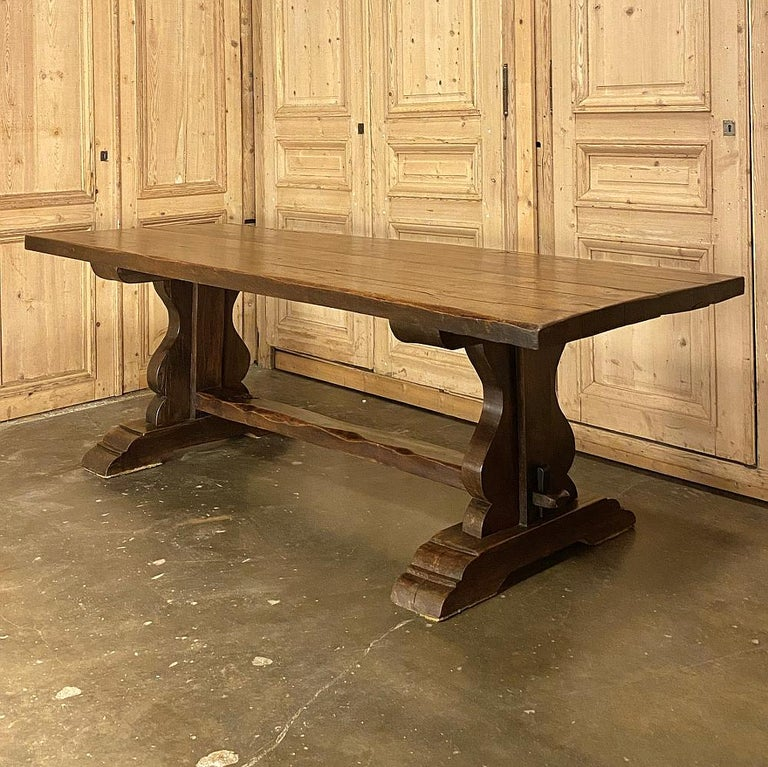 Antique country French Rustic trestle dining table was handcrafted from thick, solid timbers of old growth oak to literally last for centuries! The plank top rests on two very sturdy leg structures that tie into the top with a
