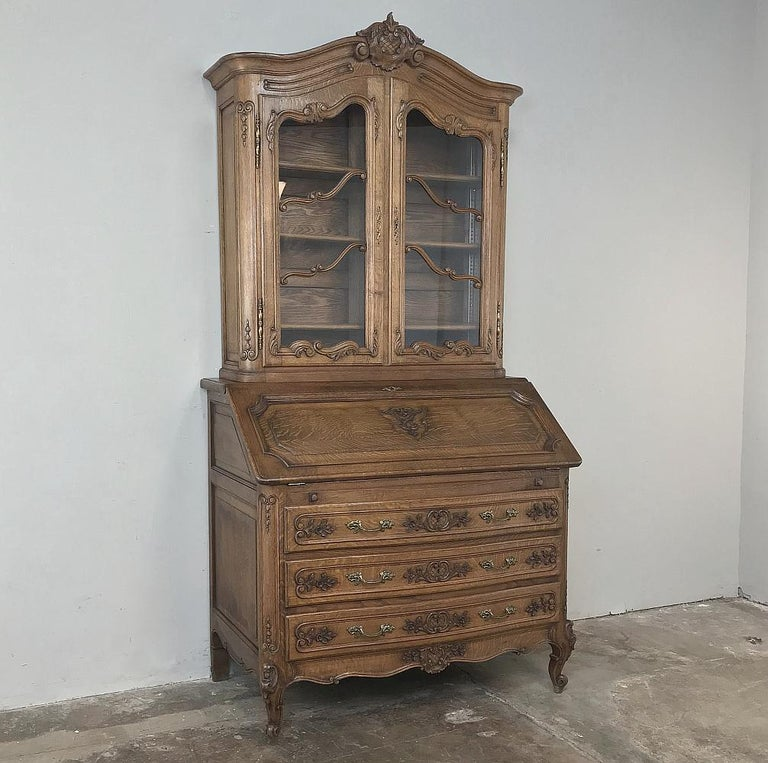 Antique Country French Secretary, bookcase is the perfect all-in-one solution! Handcrafted from solid oak to last for generations, it features an arched crown centered with a beautifully rendered crest, all presiding over the gracefully arched