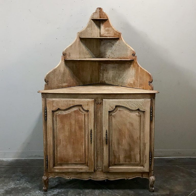 Antique Country French stripped corner cabinet is perfect for taking advantage of that otherwise unused corner space, with multiple tiers for serving or display and a modicum of storage in the cabinet below. Charming provincial look works with any