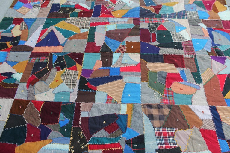 This fine embroidered and pieced crazy quilt is in fine condition and has many different patchwork wool fabrics. The condition is very good. The back is in old floral fabric. And also in good contact.