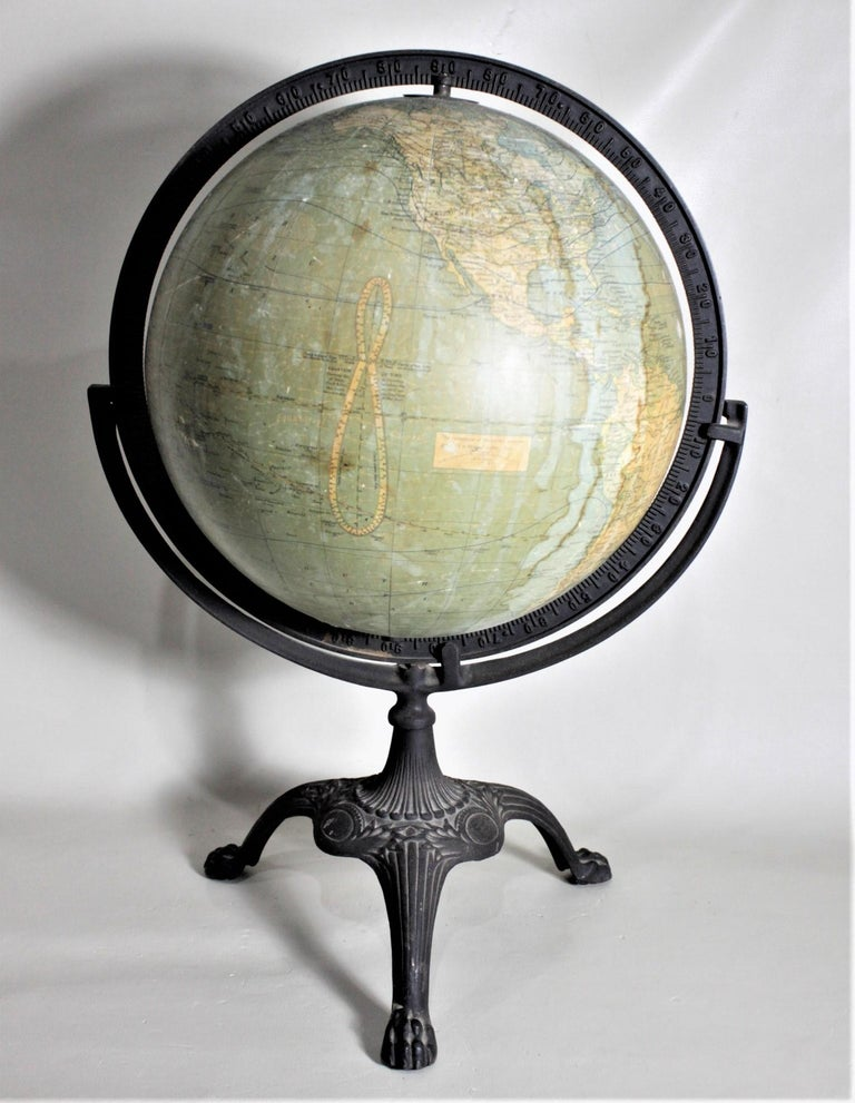 This antique desk globe was made by the C.S. Hammond & Co. of New York in approximately 1920 in the period Art Deco style. The globe sits inside a cast iron frame which rotates around, while permitting the globe to spin on its axis. The cast iron