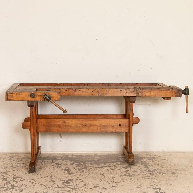 This vintage carpenters' workbench has a warm patina after years of traditional use. The scratches, dings and even touches of spilled paint add to the character of this 6' work table. It has two wrought-iron vices with wood handles and a recessed