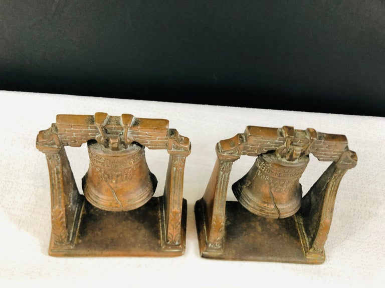 A decorative set of two antique cast bronze Mission bells sculptures. Each bell features fine details and engraving.   Perfect to decorate your desk, study room or your living room shelves.   Measures: 4.75