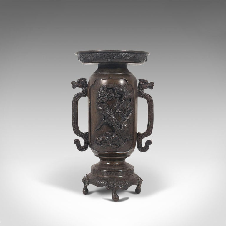 This is an antique decorative twin-handled vase. A Japanese, bronze Meiji period vase, dating to the late 19th century, circa 1900.  An impressive vase with striking detail Displaying a desirable aged patina by way of fine weathering Bronze