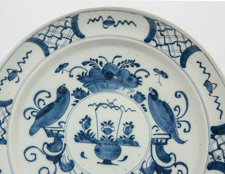 We are pleased to offer this Dutch Delft blue and white charger showing a pair of songbirds and baskets of flowers and fruit. It is painted with both dark and light tones of cobalt blue on a white ground. The contrasting tones make the decoration