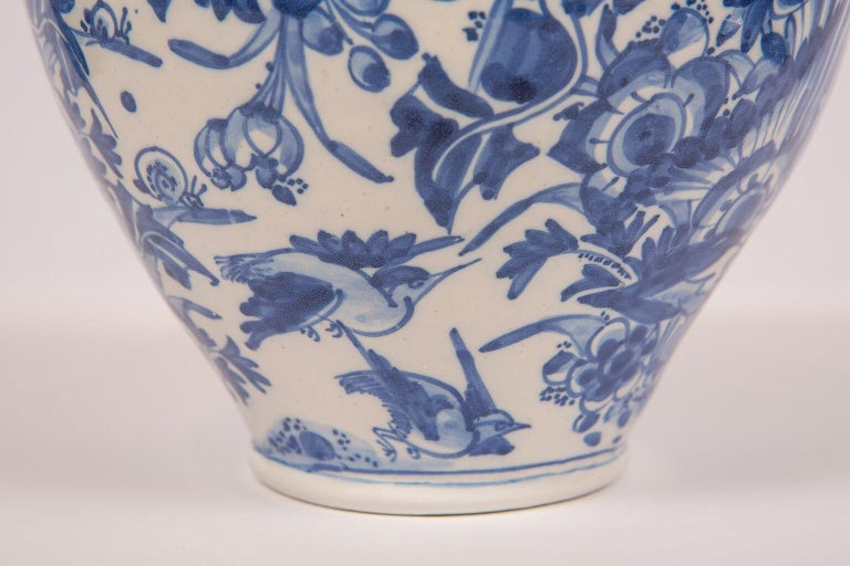 WHY WE LOVE IT:  It's 17th century-pastel blue, and well painted  Decorated with birds, butterflies, and wonderful flowers. The high quality, freehand painting style and pastel blue palette on this baluster form London Delft vase became the