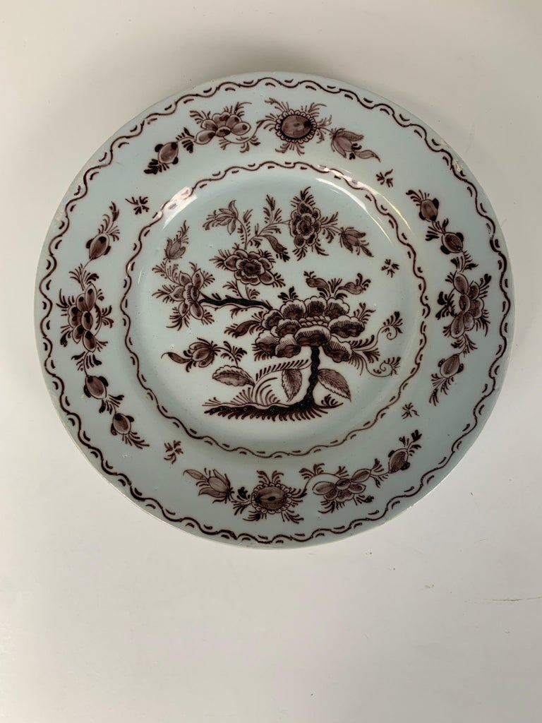 A set of five antique Dutch Delft dishes beautifully painted with manganese-based purple.  The dishes show a peony plant in full bloom. The maker was Hugo Brouwer. Brouwer created the design, and each dish would have been hand-painted in his
