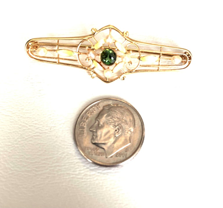 This beautiful 14k yellow gold Art Nouveau inspired pin features a very rare demantoid garnet, the rarest of all garnets. Displaying its characteristic green hue and brilliant fire, the 4.4mm demantoid garnet is framed by six 2mm white pearls and