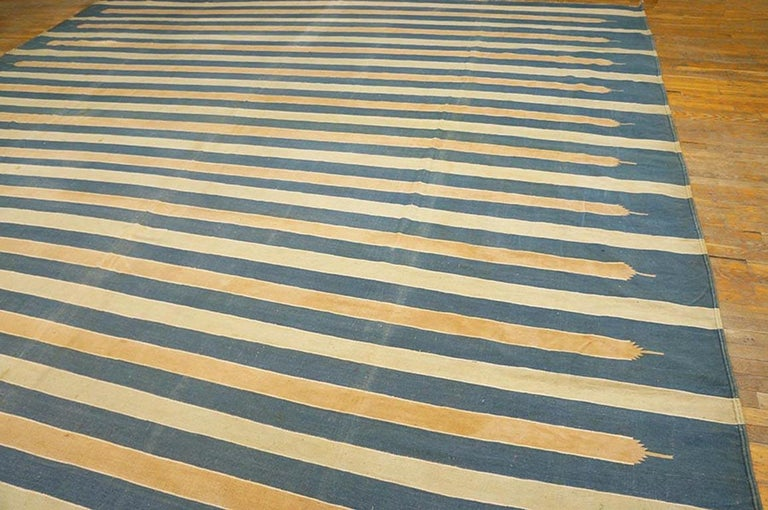 This now over square cotton flat-weave shows a washed denim blue field with full width cream stripes alternating with truncated and pointed sandy straw equal width bands. May once have been longer. Good condition Indian antique. Measures: 13'3