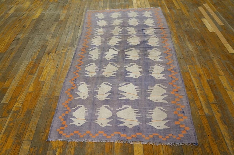 A Dhurrie for a child's room. The four columns of amusingly ambiguous hump-backed ecru animals are set on the uncommon purple ground, within an orange chessboard zig-zag border. The border color dates it circa 1920, making ikt a true antique. Good