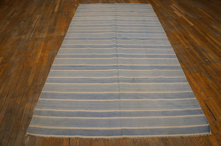 There must be 10,000 shades of Dhurrie blue and this long rug (kellegi) format piece shows a light pattern of un-bordered stripes in sky and light blue, with narrow eggshell lines between. A short step to a narrow(er) runner. Virtually antique, good